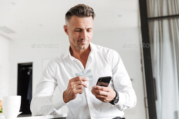 Smiling man dressed in formal clothes drinking coffee - Stock Photo - Images