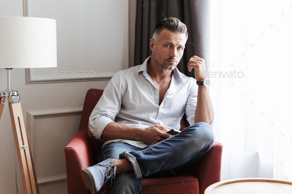 Photo of caucasian handsome man 30s in casual wear using smartph - Stock Photo - Images