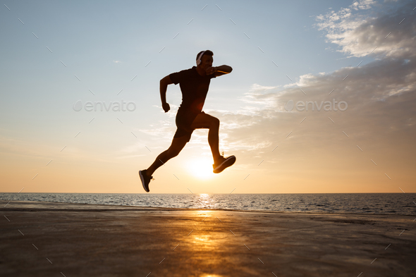 Silhouette of active sporty man 30s jumping and running along pi - Stock Photo - Images