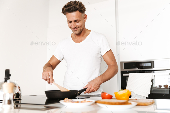 Smiling man cooking eggs for breakfast - Stock Photo - Images