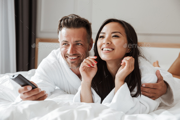 Multiethnic couple caucasian man and asian woman wearing white b Stock  Photo by vadymvdrobot
