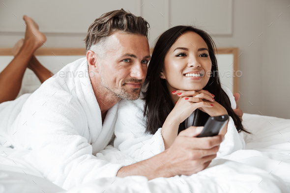 Photo of multiethnic couple man and woman wearing white bathrobe - Stock Photo - Images