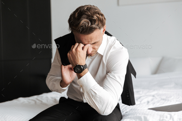 Stressed man dressed in suit sitting on bed - Stock Photo - Images