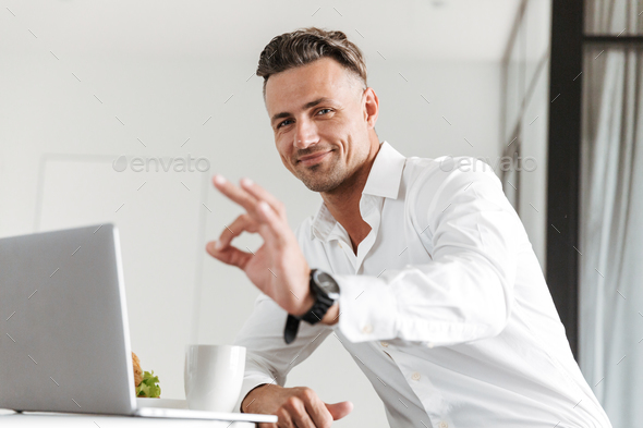 Smiling man dressed in formal clothes using laptop - Stock Photo - Images