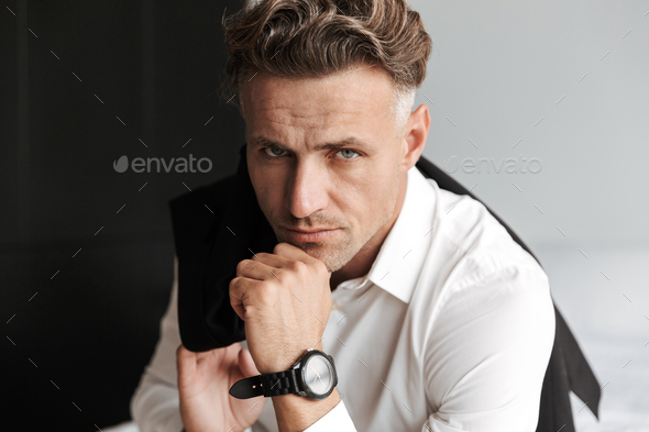 Concentrated man dressed in suit sitting - Stock Photo - Images