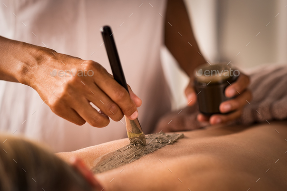 Beautician applying mud on body - Stock Photo - Images