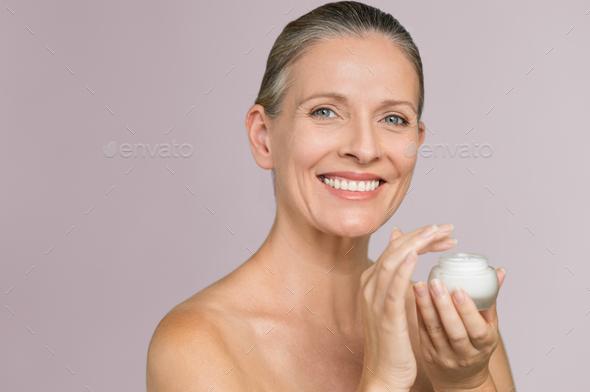 Woman holding jar of moisturizer - Stock Photo - Images