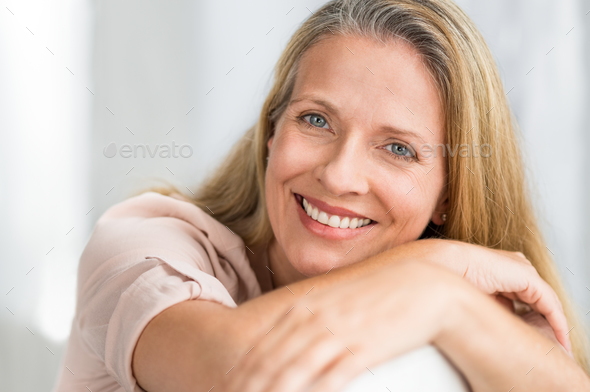 Smiling mature woman on couch - Stock Photo - Images