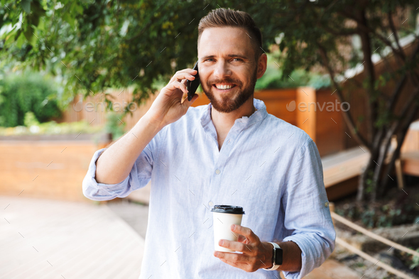 Happy young bearded man talking by mobile phone - Stock Photo - Images