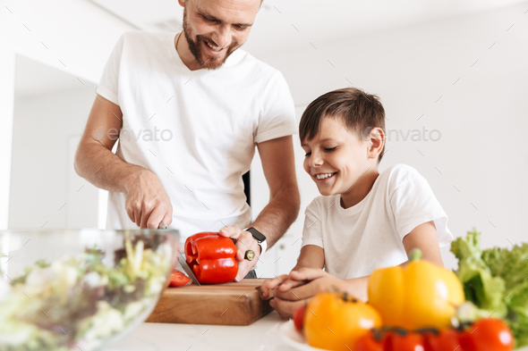Cheerful young man father dad cooking with his son - Stock Photo - Images