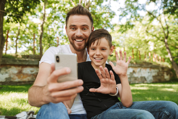 Happy young father sitting with his little son using mobile phone. - Stock Photo - Images