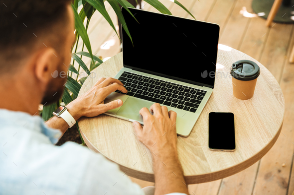 Cropped image of young bearded man using laptop - Stock Photo - Images