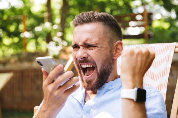 Young bearded man outdoors using mobile phone - Stock Photo - Images