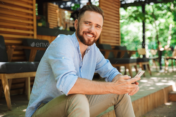 Emotional young bearded man outdoors using phone looking camera. - Stock Photo - Images