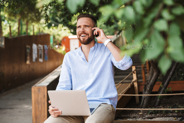 Smiling emotional young bearded man talking by mobile phone. - Stock Photo - Images