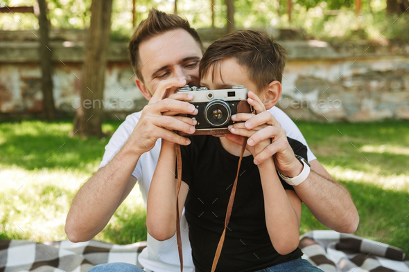Young father sitting with his little son holding camera photographing. - Stock Photo - Images