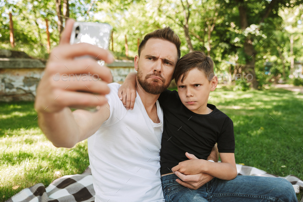 Funny young father sitting with his little son make selfie by mobile phone. - Stock Photo - Images