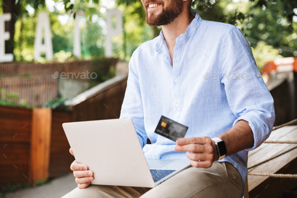 Smiling emotional young bearded man using laptop - Stock Photo - Images
