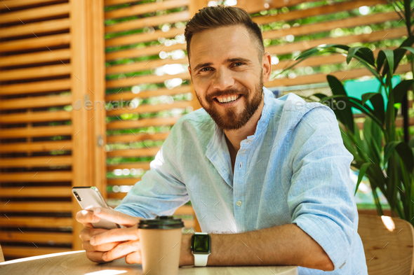 Happy young bearded man in cafe drinking coffee looking camera. - Stock Photo - Images