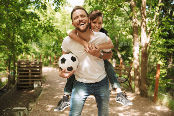 Happy young father have fun with his little son with football - Stock Photo - Images
