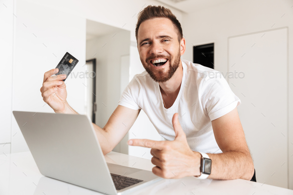 Young man using laptop computer holding credit card - Stock Photo - Images