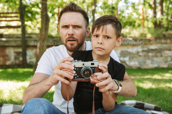 Young confused father sitting with his little son photographing. - Stock Photo - Images