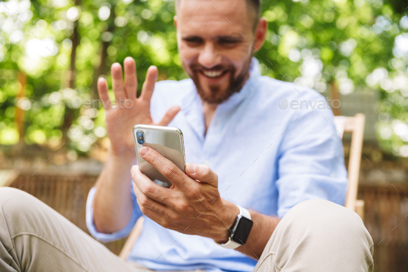 Happy young bearded man outdoors talking by mobile phone. - Stock Photo - Images