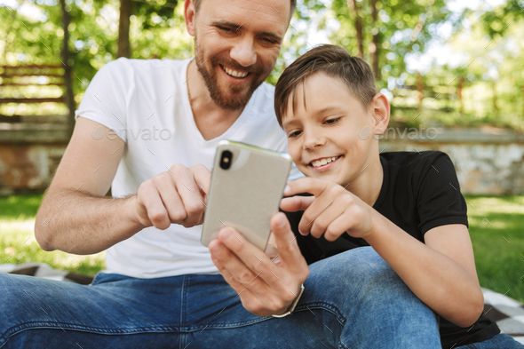 Cheerful young father sitting with his little son using mobile phone. - Stock Photo - Images