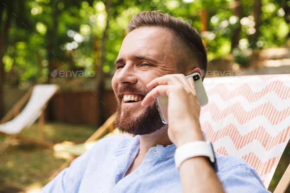 Happy young bearded man outdoors talking by phone. - Stock Photo - Images