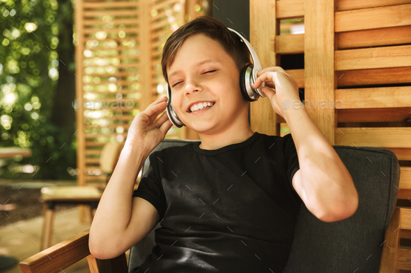 Cheerful boy sitting in cafe nature listening music - Stock Photo - Images