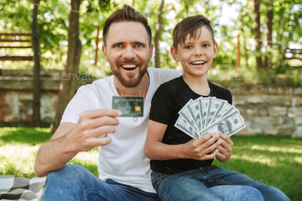 Happy excited young father sitting with his little son holding money and credit card. - Stock Photo - Images
