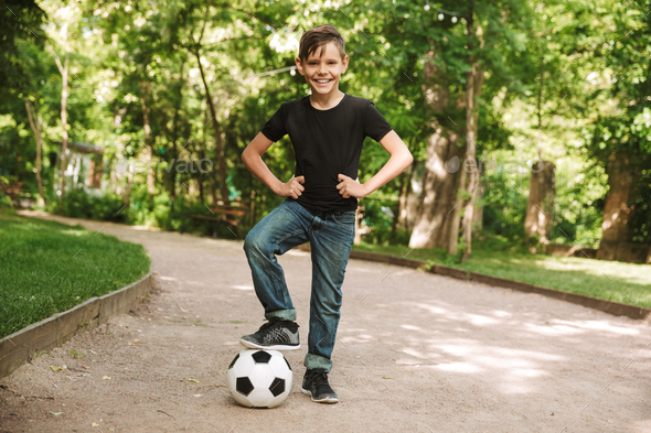 Happy little boy outdoors in park nature play football - Stock Photo - Images