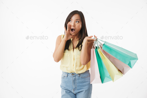 Emotional young asian woman with shopping bags make speaking gesture. - Stock Photo - Images
