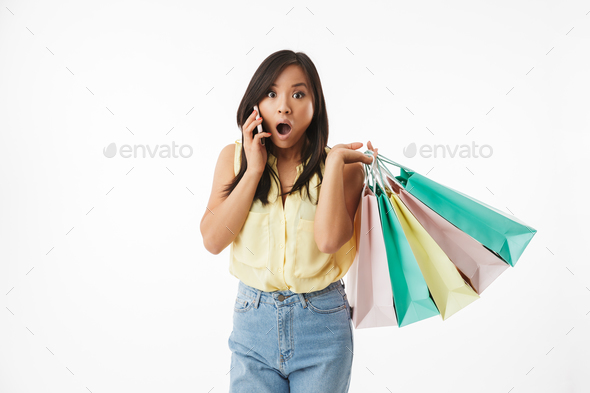 Shocked young asian woman with shopping bags talking by mobile phone. - Stock Photo - Images