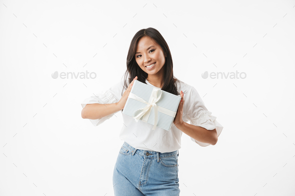 Image of happy birthday asian girl 20s smiling and holding prese - Stock Photo - Images