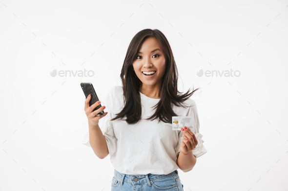 Joyous asian woman wearing casual clothing looking at camera wit - Stock Photo - Images