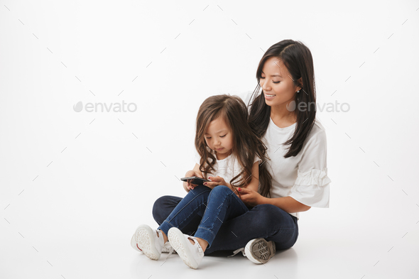 Happy young asian woman mother with daughter using mobile phone. - Stock Photo - Images