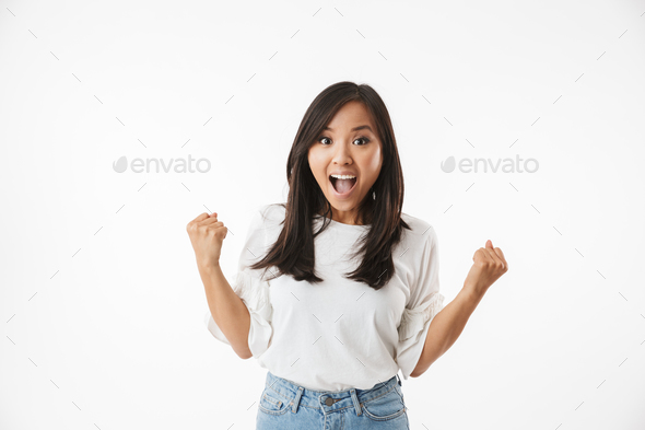 Excited pretty young asian woman showing winner gesture. - Stock Photo - Images