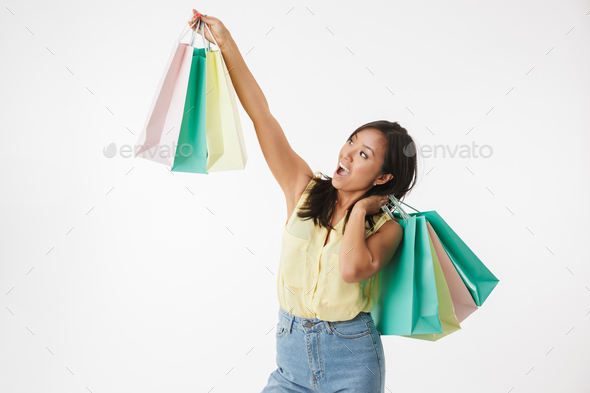 Excited young asian woman with shopping bags. - Stock Photo - Images