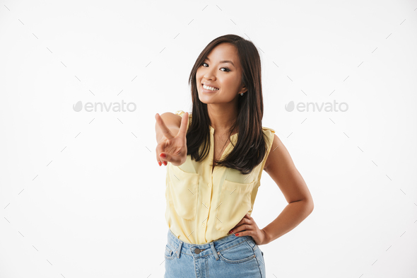 Happy young asian woman showing peace gesture. - Stock Photo - Images