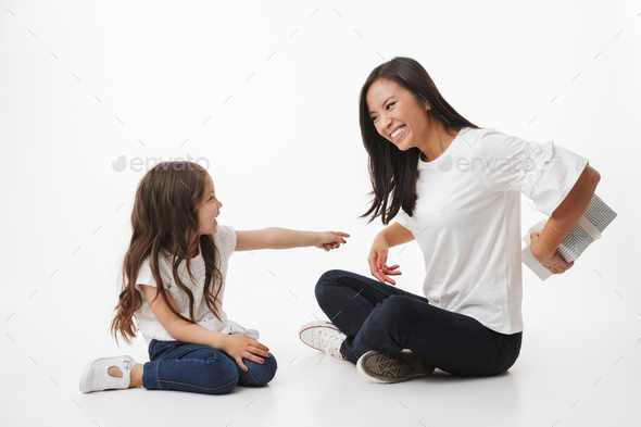 Cute young asian woman mother gives a present gift box to her little girl child daughter - Stock Photo - Images