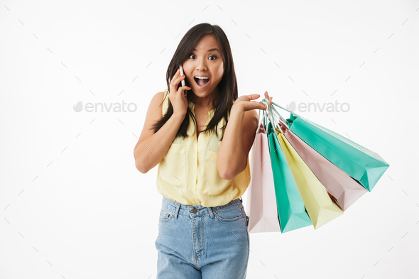 Emotional young asian woman with shopping bags talking by mobile phone. - Stock Photo - Images