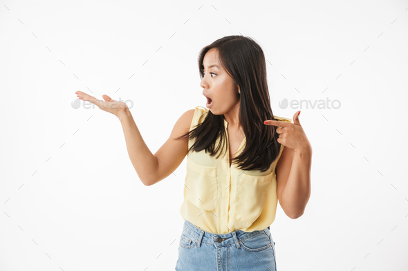 Excited young asian woman pointing. - Stock Photo - Images
