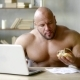 Muscleman Is Eating Hamburger and Browsing in Internet Using Laptop, Sitting at a Table in Home - VideoHive Item for Sale