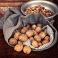 Whole walnuts in bag on the background walnut kernels in the bow - PhotoDune Item for Sale