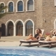 Group of Young Women Having a Sun Bath, Lying on Deckchair Near the Hotel Pool - VideoHive Item for Sale