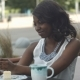 Attractive Young African Woman Smiling and Taking a Selfie with Her Smartphone While Sitting Alone - VideoHive Item for Sale