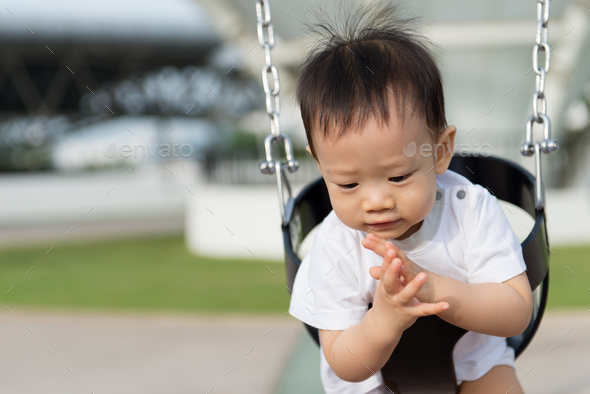 Little Asian boy in swing - Stock Photo - Images
