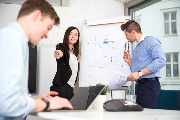 Businesswoman Pointing At Male Colleague Using Laptop - Stock Photo - Images