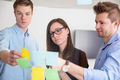 Business Colleagues Discussing Over Adhesive Notes Stuck On Glas - PhotoDune Item for Sale